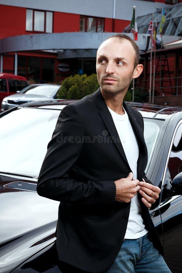 衣服的时髦的人在黑汽车附近 室外的商人 Succes 库存图片