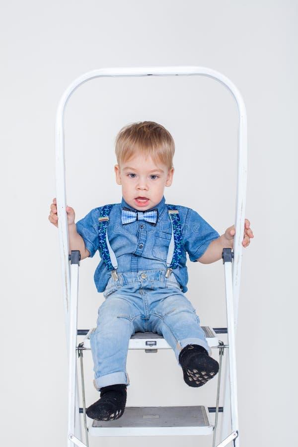 衣服的男孩坐活梯 免版税库存照片