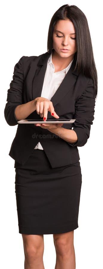 衣服的美丽的女实业家使用片剂 图库摄影