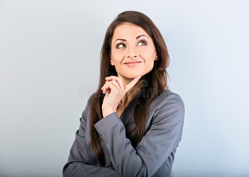 衣服的美丽的成功女商人与在面孔下的手指和看想出在蓝色背景的 r 库存图片