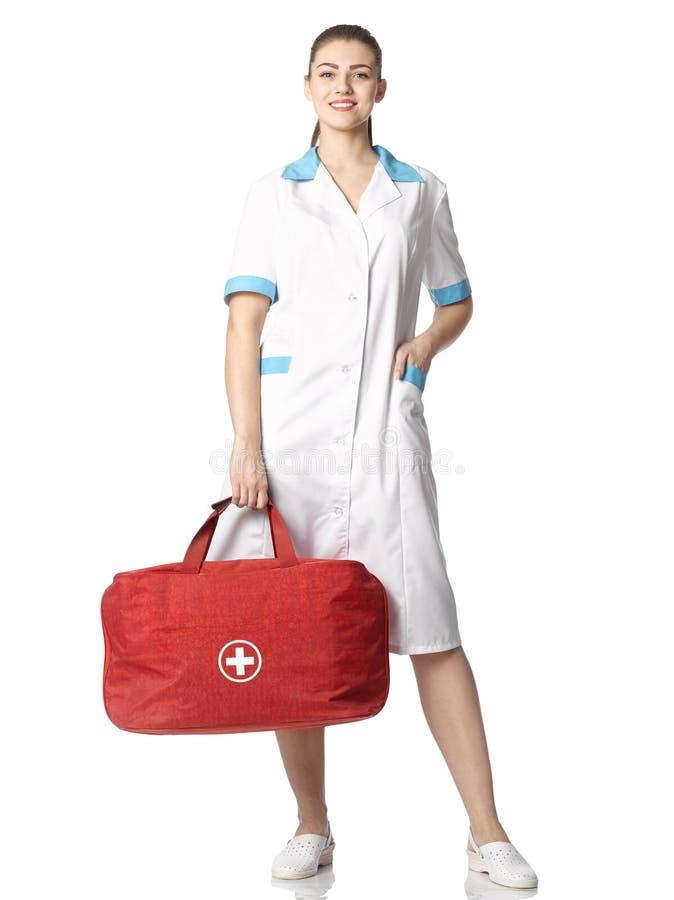 衣服的美丽的护士女孩与红色袋子和白色十字架 免版税库存照片