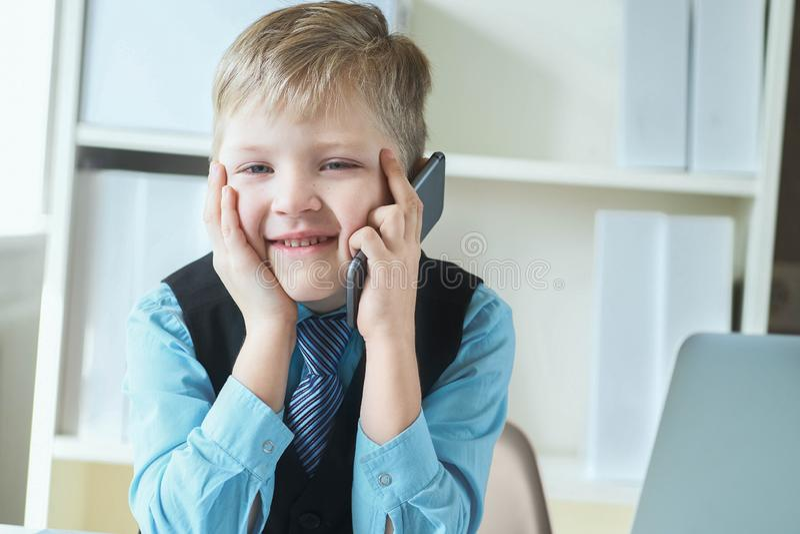 衣服的聪明的小男孩研究计算机,采取笔记和情感地说在电话里 图库摄影