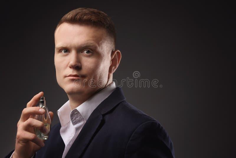 衣服的英俊的人使用香水 库存照片