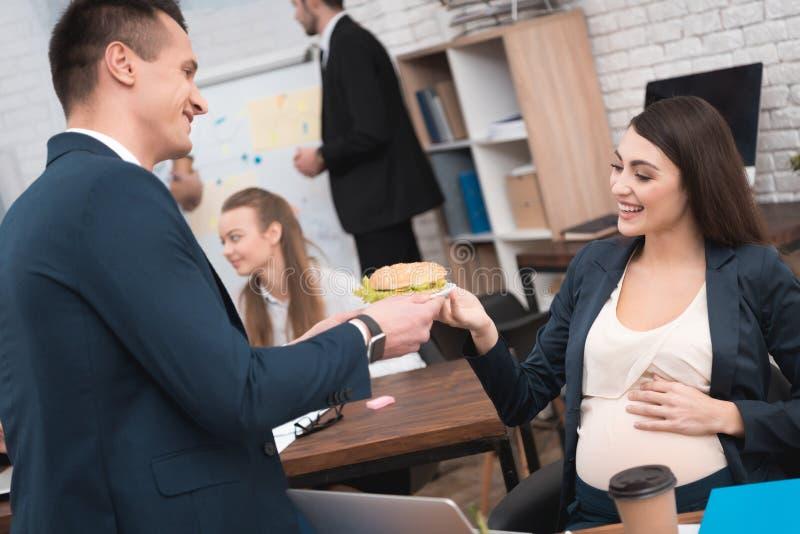 衣服的英俊的人给三明治年轻孕妇在办公室 怀孕在工作 免版税库存照片