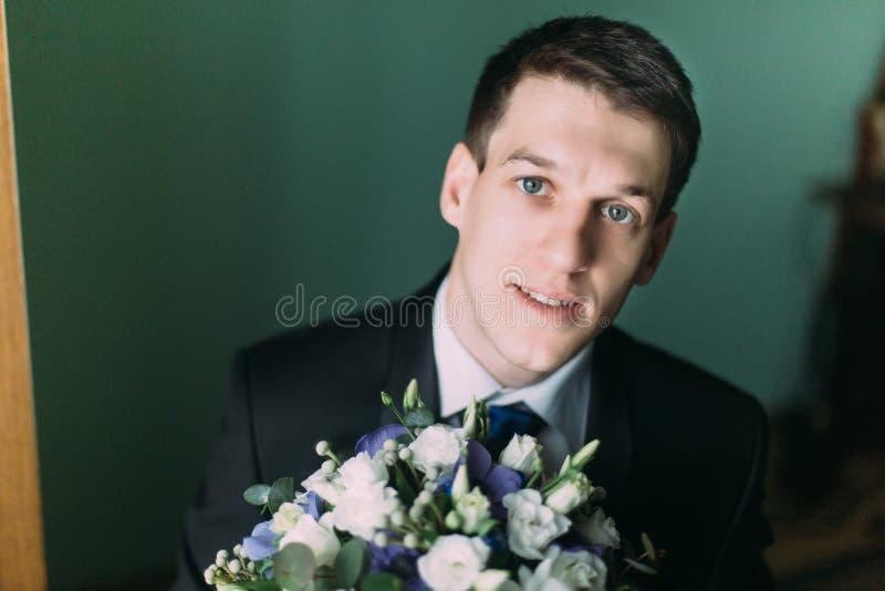 黑衣服的英俊的典雅的新郎与婚礼花束特写镜头 免版税库存图片