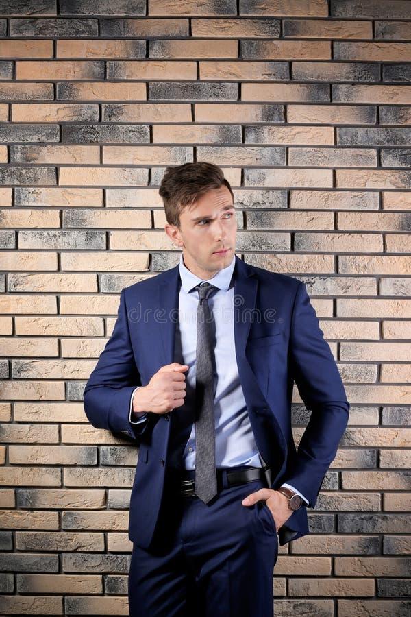 衣服的英俊的年轻人在墙壁背景附近 库存图片
