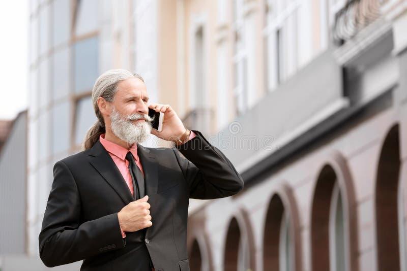 衣服的英俊的成熟人与手机 免版税库存照片