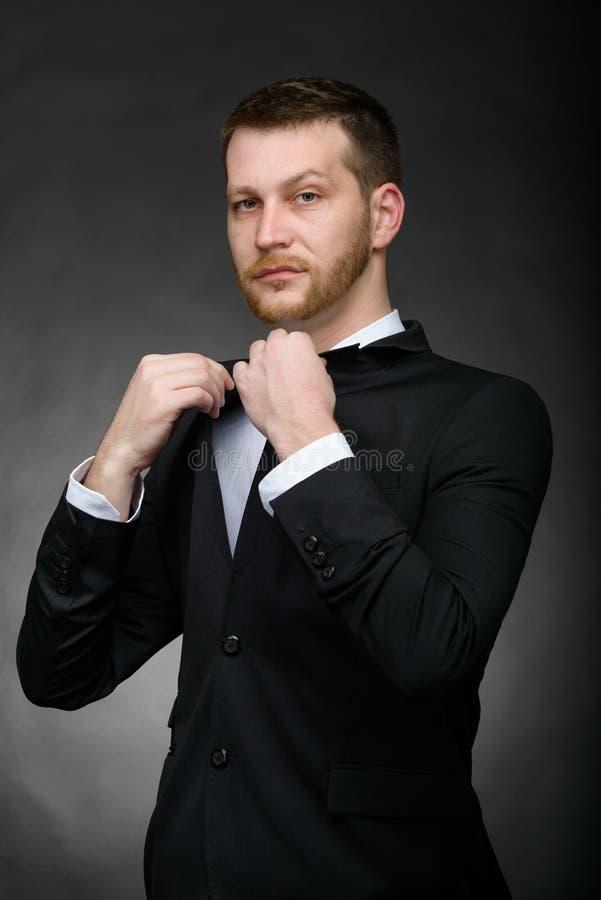 黑衣服的英俊的确信的商人 库存照片