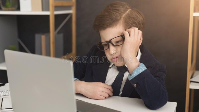 衣服的被用尽的小商人在与膝上型计算机的桌上 库存图片
