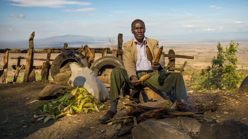 衣服的非洲人在东非大裂谷附近卖玉米  库存照片