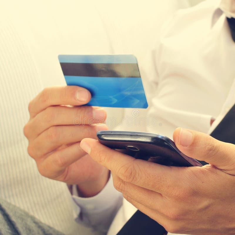 衣服的年轻人使用在网上他的信用卡 免版税图库摄影