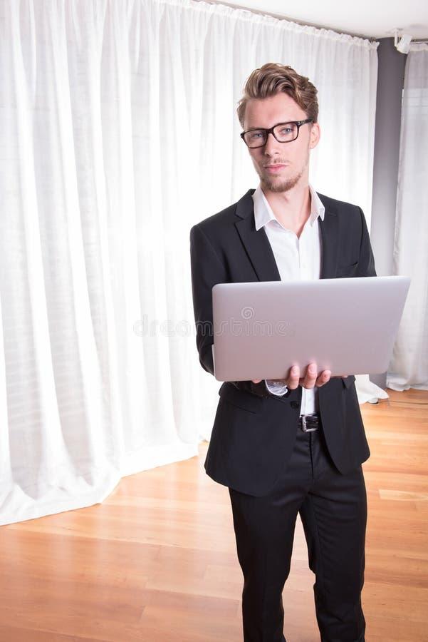 衣服的画象年轻商人与膝上型计算机一起使用 免版税图库摄影