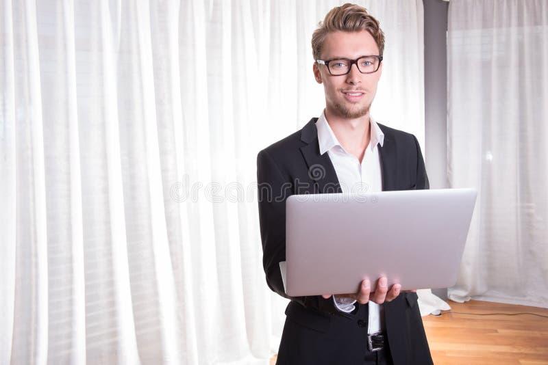 衣服的画象年轻商人与膝上型计算机一起使用 免版税库存图片