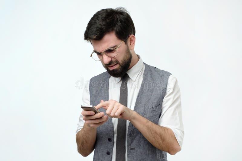 衣服键入的sms的严肃的人在智能手机 图库摄影