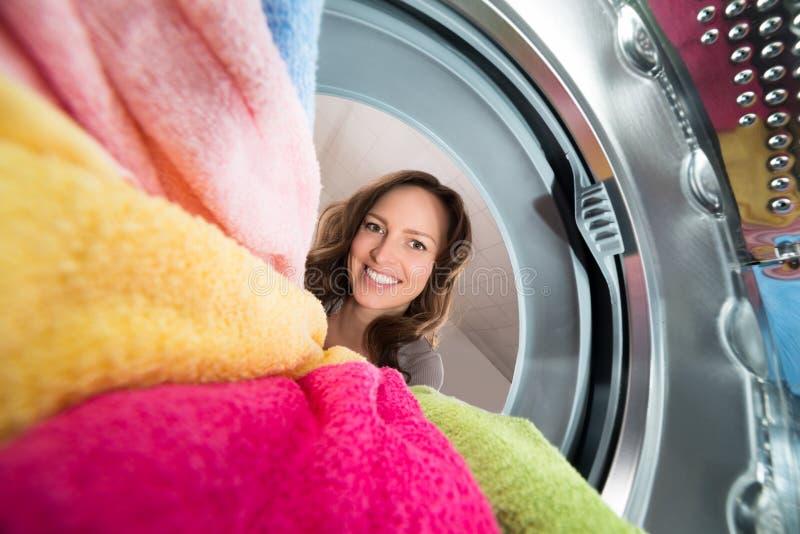 从洗衣机里边的愉快的妇女景色 免版税图库摄影