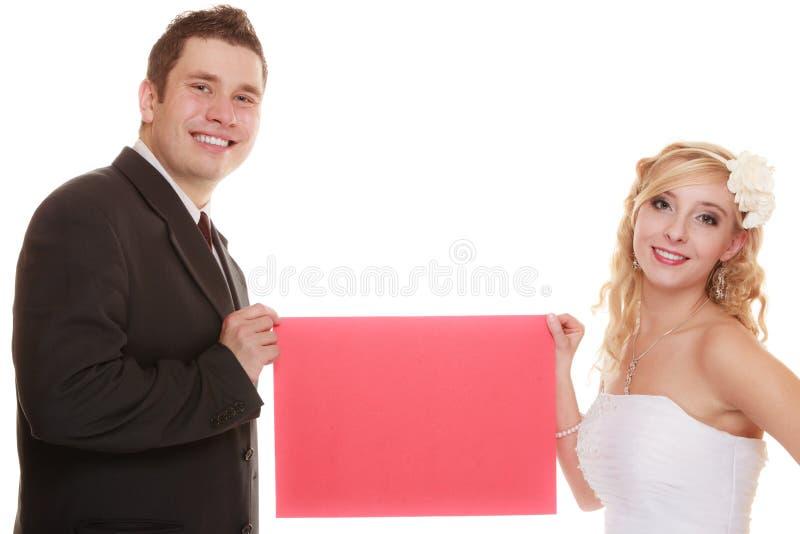 衣物夫妇日愉快的葡萄酒婚礼 拿着标志红色空白的新娘和新郎 免版税图库摄影