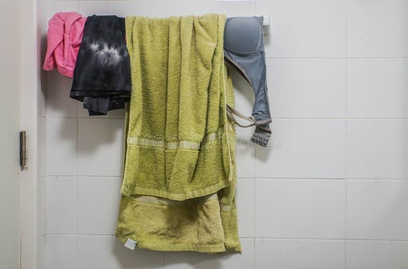 衣裳、胸罩和绿色毛巾在垂悬的机架在卫生间里 免版税库存图片