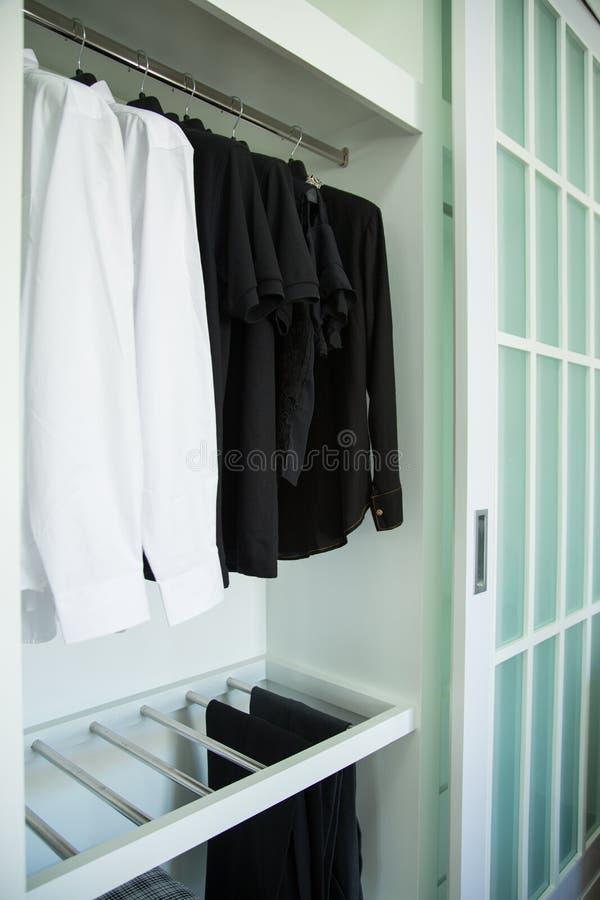 衣裳在一个架子在名牌服装商店,与布料垂悬在衣橱的,葡萄酒房间行的现代壁橱垂悬  免版税库存照片