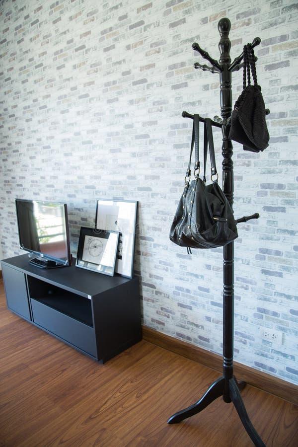 衣裳在一个架子在名牌服装商店,与布料垂悬在衣橱的,葡萄酒房间行的现代壁橱垂悬  免版税库存图片