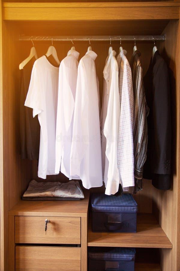 衣裳在一个架子在名牌服装商店,与衣裳垂悬在衣橱的,葡萄酒房间行的现代壁橱垂悬  免版税库存图片