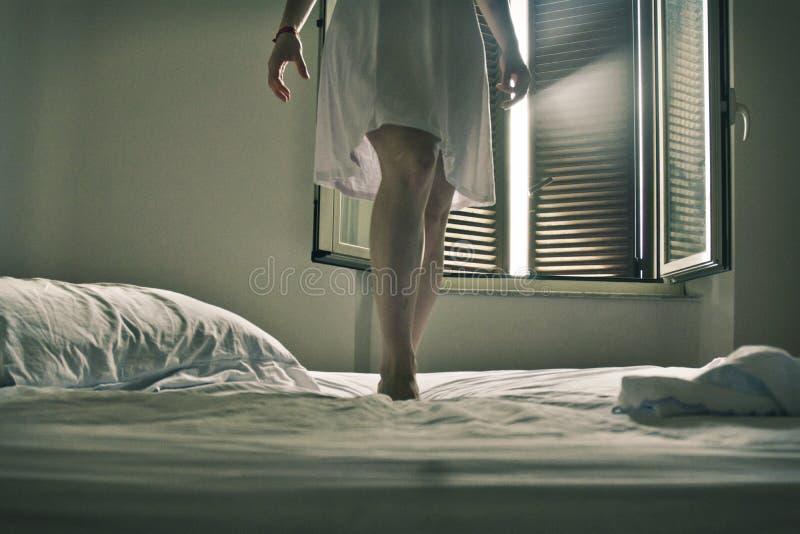 衣裳在一张白色床放置了在白色身分打扮的妇女的oLegs 库存照片
