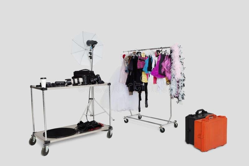 衣裳在演播室折磨和带着手提箱的反射器伞 库存照片