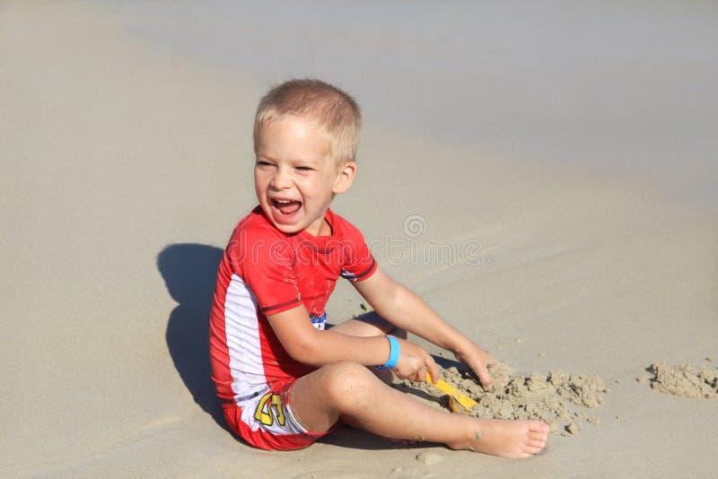 衣裳的一个小男孩有紫外过滤器的使用与在海滩的沙子由海,与孩子的假日,保护孩子从 免版税图库摄影