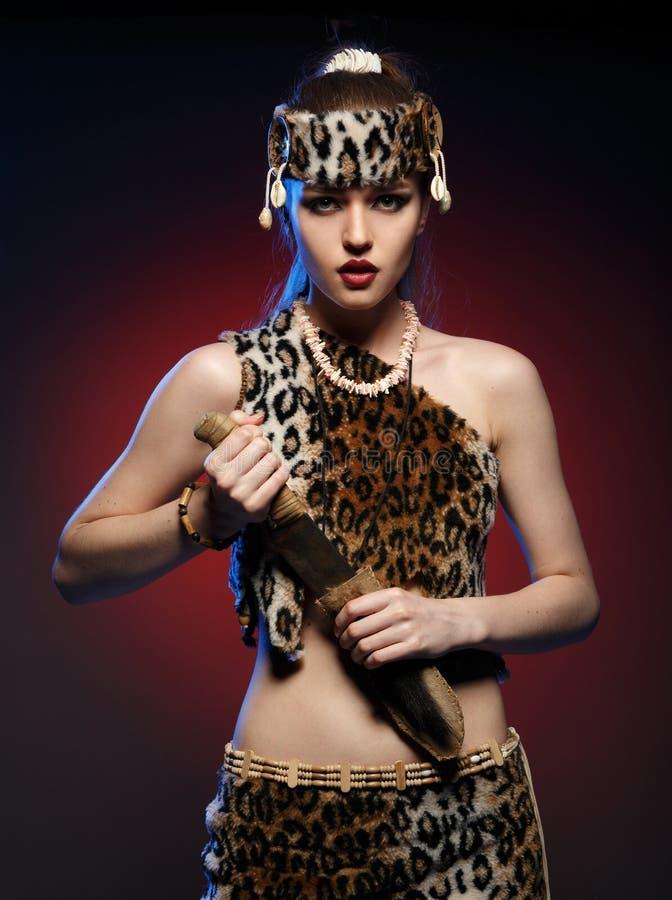衣裳的亚马逊女孩有一把刀子的在他的手上 库存照片