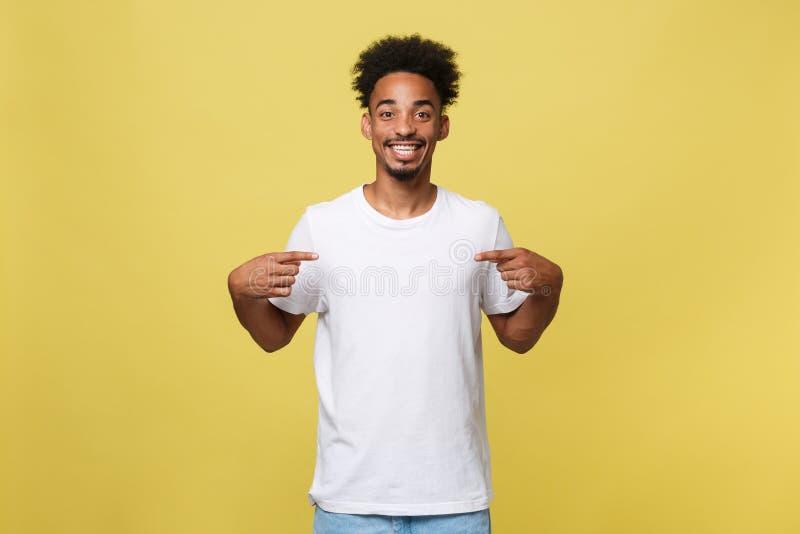 衣裳的英俊的快乐的深色皮肤的男性卖主画象,打扮在偶然白色T恤杉,表明在空白 免版税图库摄影