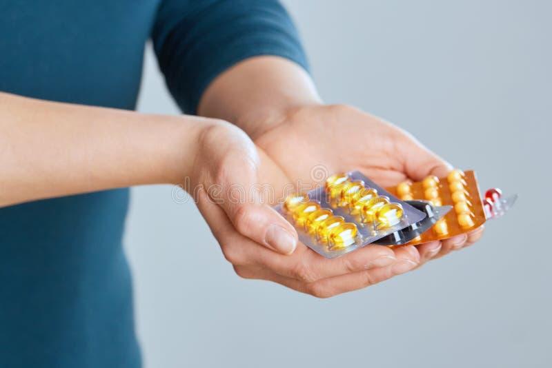 补充维生素 举行五颜六色的药片的品种在棕榈的女性手特写镜头 特写镜头妇女手指采取 库存图片