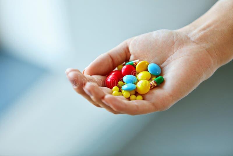 补充维生素 有五颜六色的药片的女性手 图库摄影