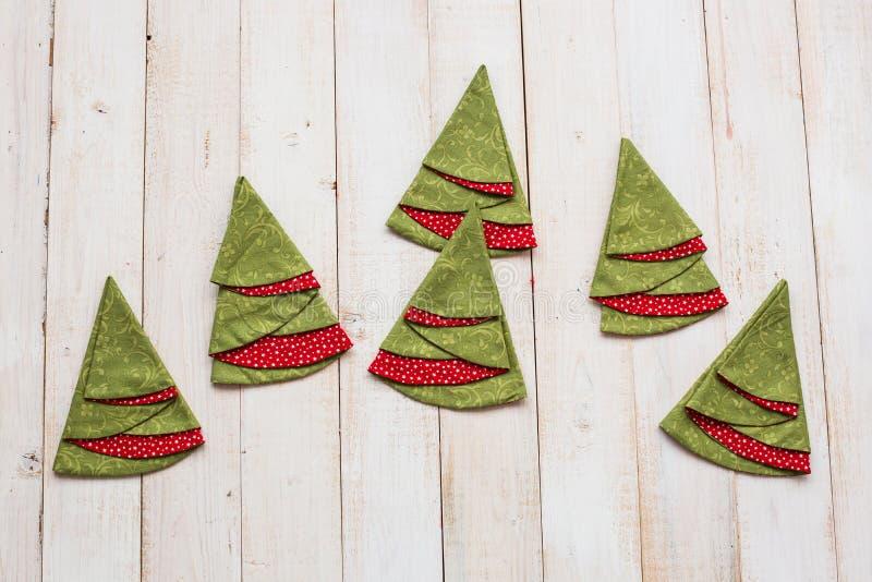 补缀品,缝制和时尚概念-在一个被粉刷的木地板上的五颜六色的装饰红和绿的餐巾 免版税库存照片