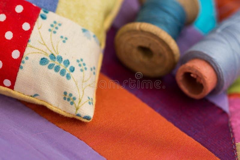 补缀品,缝制,缝合,剪裁和时尚概念-在美丽的五颜六色的被缝的坐垫和螺纹的特写镜头 免版税库存照片