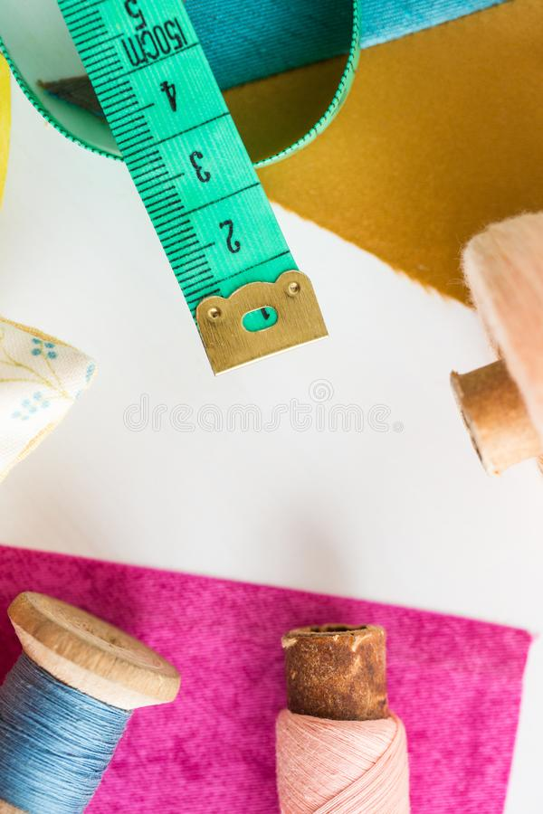 补缀品,缝合和剪裁概念-在工具、测量的米、蓝色和桃红色的特写镜头在片盘穿线和 免版税图库摄影