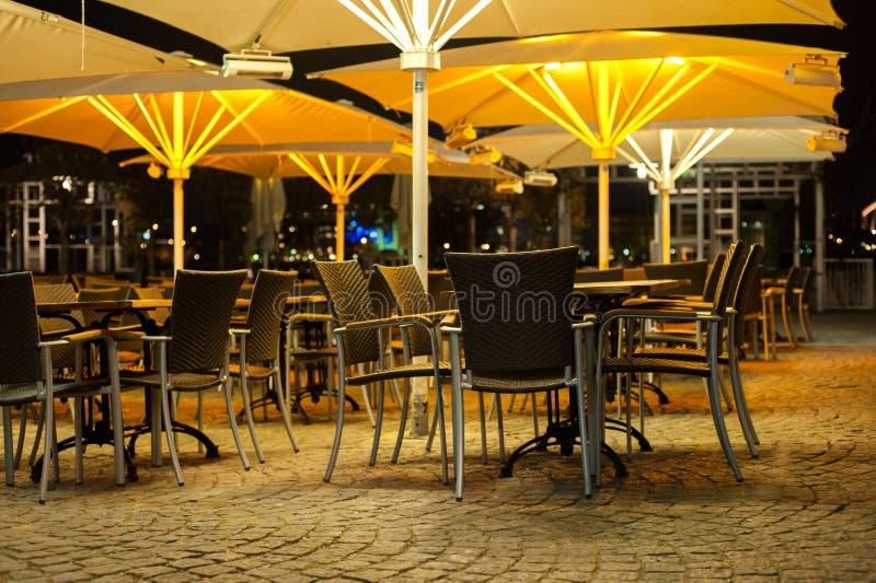 表和椅子一家餐馆外在晚上 免版税库存图片