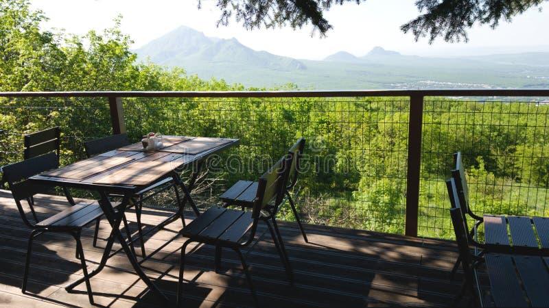 表和椅子其中一家街道餐馆有领域和山的美丽的景色 浪漫会议和室外 图库摄影