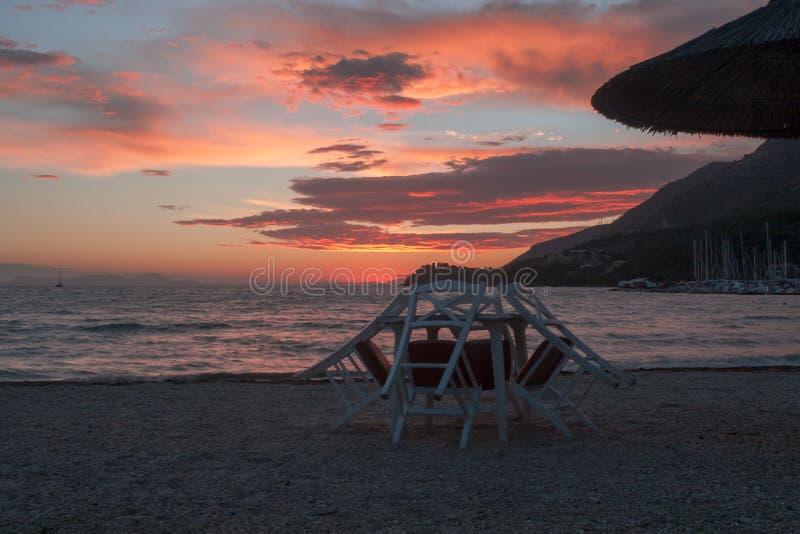 表和椅子在日落在科孚岛海岛 免版税库存照片