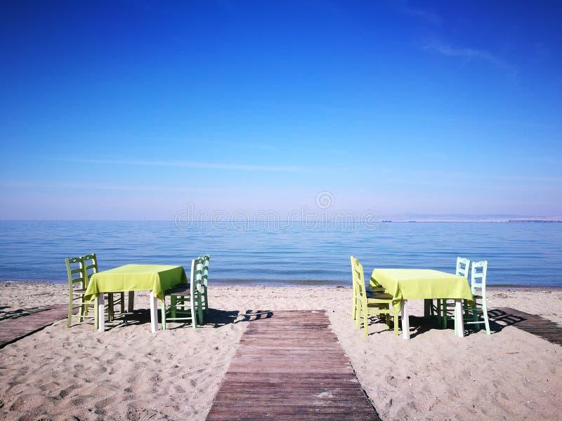 表和椅子在沙子海滩 免版税库存图片