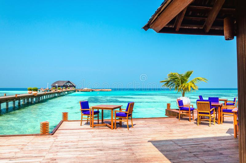 表和椅子在高跷的一家木餐馆在天蓝色的水和蓝天背景  免版税库存图片