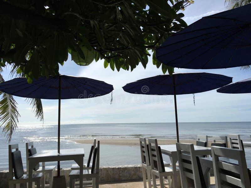 表和沙滩伞由海sundawn的在Huahin,泰国 免版税图库摄影