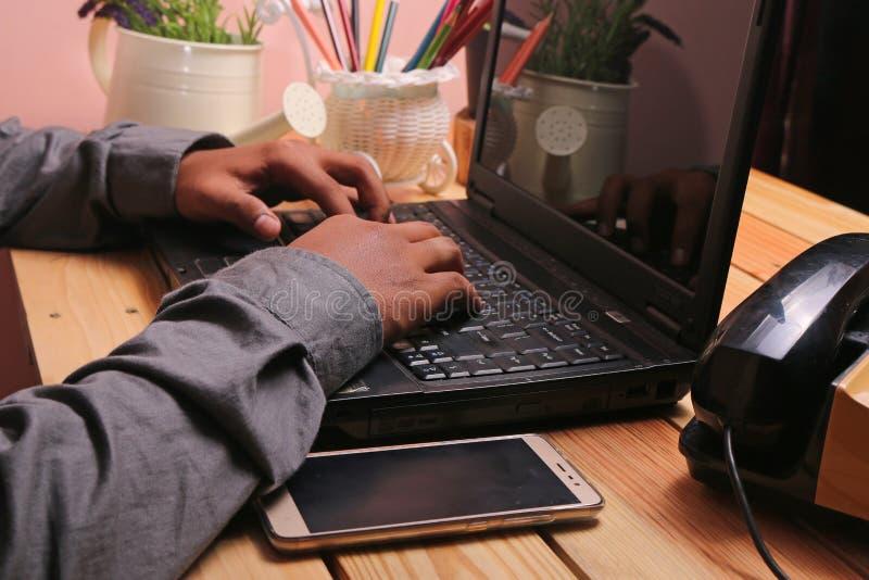 表和膝上型计算机有装饰品的例如花瓶和电话 免版税图库摄影