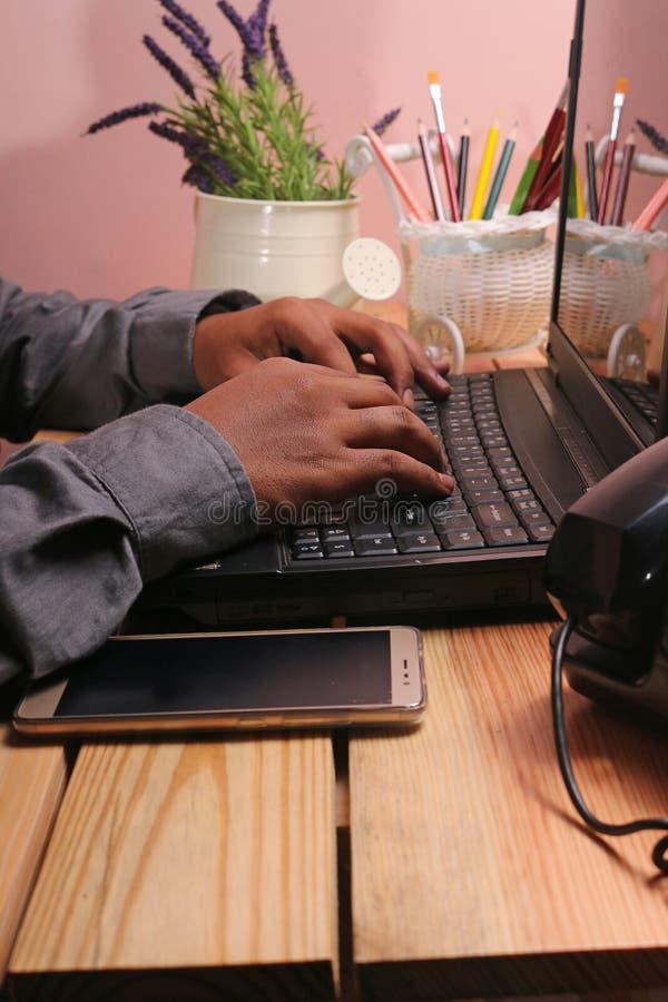 表和膝上型计算机有装饰品的例如花瓶和电话 免版税库存照片
