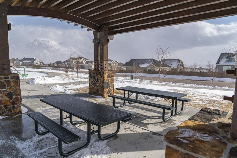 表和长凳在一个亭子里面一个多雪的公园的在一个晴朗的冬日 库存图片