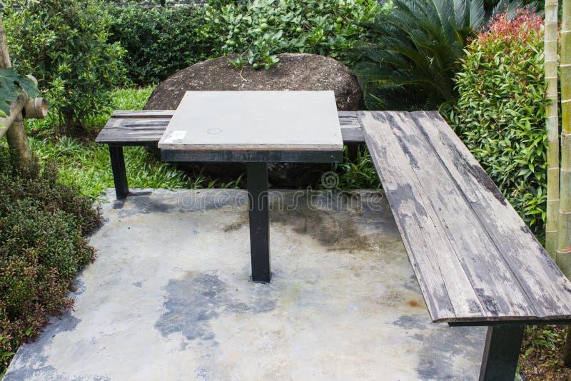 表和长的木椅子在水泥在庭院里研了有自然背景 库存图片