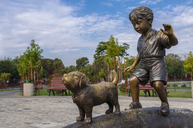 代表孩子和狗的古铜色雕象 库存照片