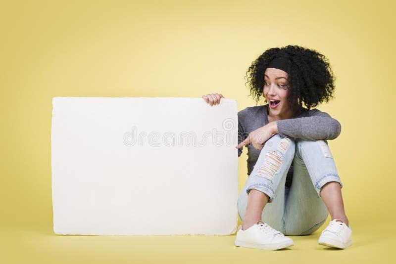 表明一个白皮书板的激动的妇女 库存照片