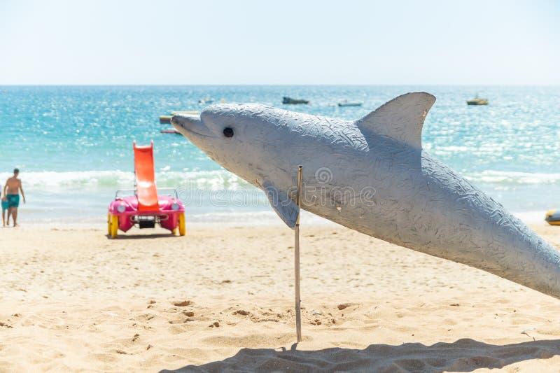 表明海豚在阿尔布费拉海滩的海豚雕塑手表机会,阿尔加威,葡萄牙 库存图片