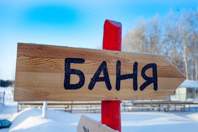 表明蒸汽浴的方向的标志 俄罗斯,冬天 在板材的题字在俄国蒸汽浴 免版税库存照片