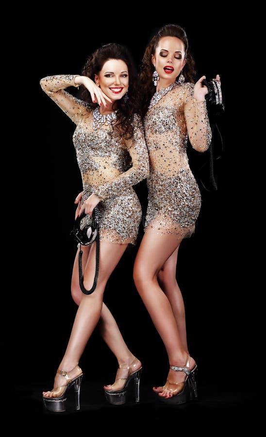 表现。戏剧性服装的两名愉快的妇女在平台鞋子 免版税库存图片