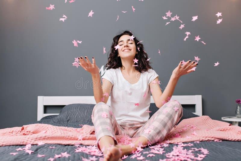 表现出年轻快乐的妇女的真实的正面情感用有被剪的卷发的睡衣获得乐趣在下跌的桃红色 免版税库存图片
